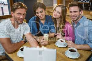Happy friends taking selfie on mobile phone while having coffee
