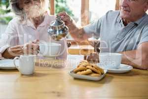 Senior man pouring tea into cup
