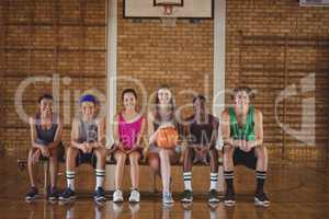 High school kids sitting on a bench in basketball court