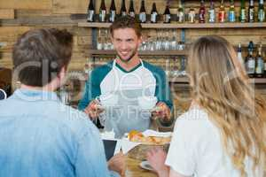 Smiling waiter serving cup of coffee to customers at counter