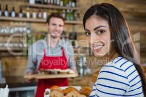 Portrait of smiling woman with waiter standing in background