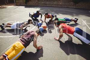 Basketball players performing push up exercise
