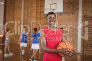 Smiling school boy holding a basketball while team playing in background