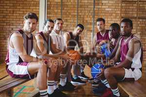 Confident coach and basketball player sitting on bench