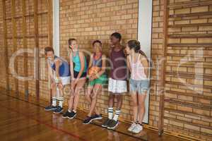 High school kids talking while leaning against the wall in basketball court