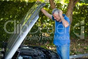 Senior man checking engine of breakdown car