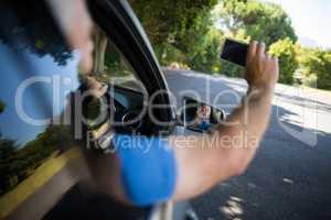 Senior man taking selfie while driving car