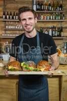 Portrait of waiter holding food at counter