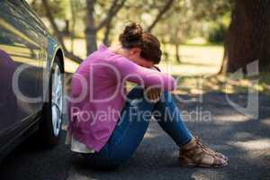 Woman sitting by breakdown car
