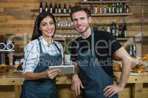 Portrait of waiter and waitresses using digital tablet at counter