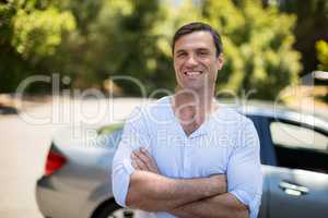 Man with arms crossed standing by car