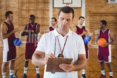 Coach writing on clipboard while team interacting in background