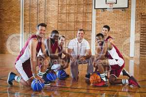 Coach and players kneeling with basketball in the court