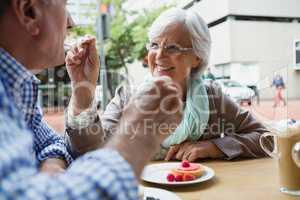 Senior woman feeding sweet food to man in caf�©
