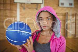 High school girl standing with basketball in the court