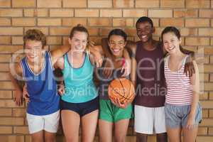 Happy high school kids with arms around leaning against the wall in basketball court