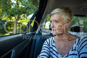 Senior woman looking through car window