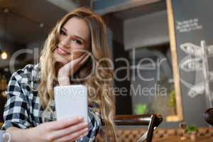 Portrait of smiling woman holding smart phone while sitting at table