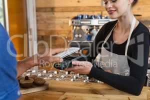 Close up of man making payment on credit card reader machine