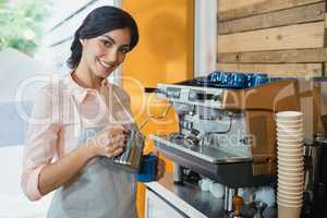 Portrait of waitress pouring coffee into cup