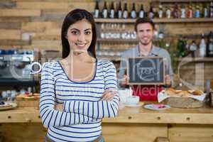 Woman standing with arms crossed while waiter holding open signboard