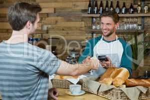 Smiling waiter receiving credit card of customer for payment at counter