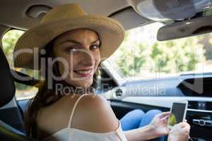 Portrait of young woman using phone in car