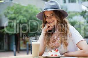 Portrait of beautiful woman sitting by food at table