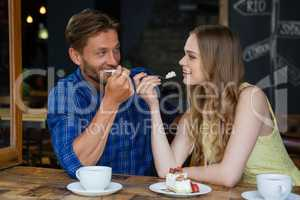 Happy couple eating sweet food while siitting at table