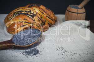 Poppy seeds in a brown wooden spoon