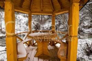 Snow covered wooden arbor .