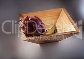 Fresh Artichoke in a square wooden plate.