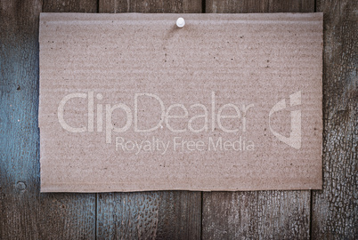 Piece of brown kraft paper hanging on a wooden wall