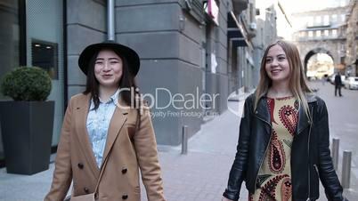 Cute shopping women walking with bags on street