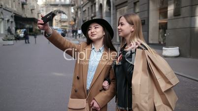 Young positive women making selfie with smartphone