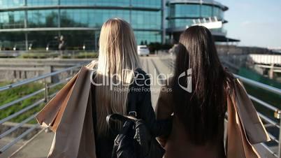 Shopaholic females walking on bridge at sunset