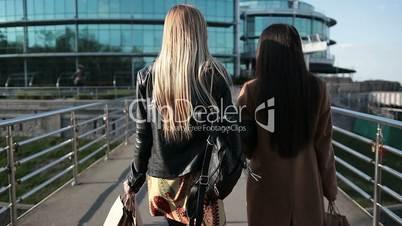 Shopping women walking on pedestrian bridge