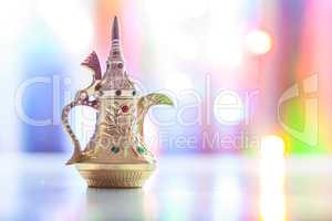 Silver Arabic Coffee pot in colorful illuminated background.