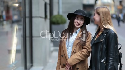 Two young women looking at clothing store window
