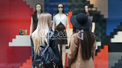 Rear view of cute girls looking at store display