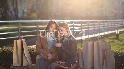 Two girls texting with friends in social network