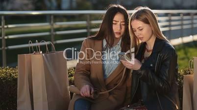 Smiling women browsing internet on mobile phone
