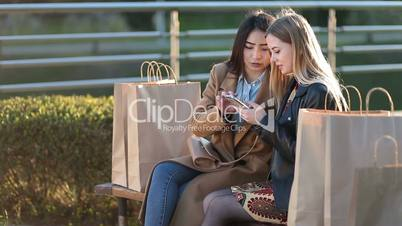 Two female friends shopping online with smartphone