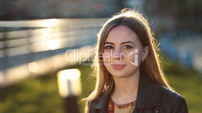 Portrait of young female with shy smile outdoors