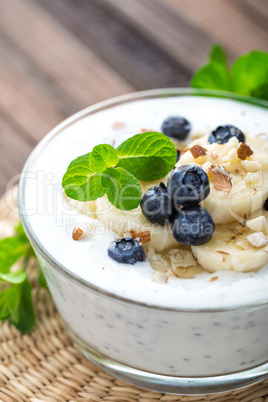 Yogurt with fresh blueberry, banana and almond nuts, delicious dessert for healthy breakfast