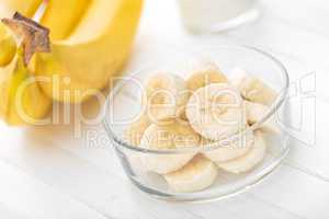 Fresh sliced bananas on white wooden background closeup, healthy eating