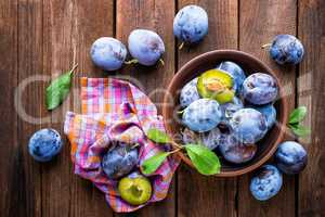Fresh plums with green leaves on wooden rustic background, top view