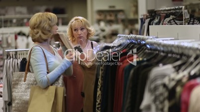 Two women shopping clothes in fashion department