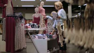 Positive female friends choosing clothes in shop