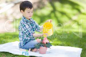 Mixed Race Young Boy Watering His Potted Flowers Outside On The